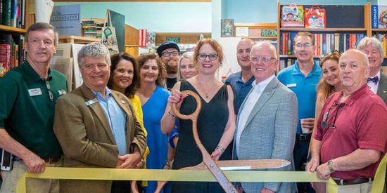Melinda Humphreys with Mayor Woody Washam (she is holding the ceremonial scissors) and friends at a chamber ribbon-cutting